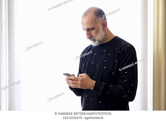 Man looking at his smarthphone in a light interior