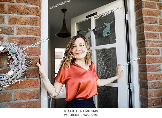 Portrait of smiling woman at house entrance