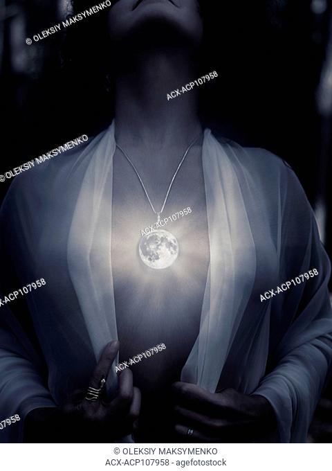Young woman wearing a magical full moon pendant glowing on her bare chest at night, artistic supernatural spiritual concept