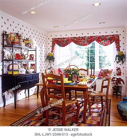 DINING ROOM: French Country with floral valance hanging over bay window., busy sideboard with display shelves fllled with colorful ceramics, place settings