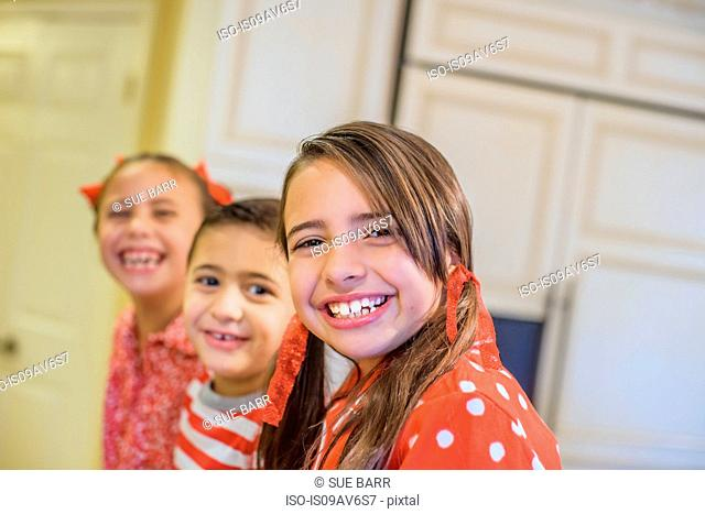 Angled view of children wearing pyjamas looking at camera smiling