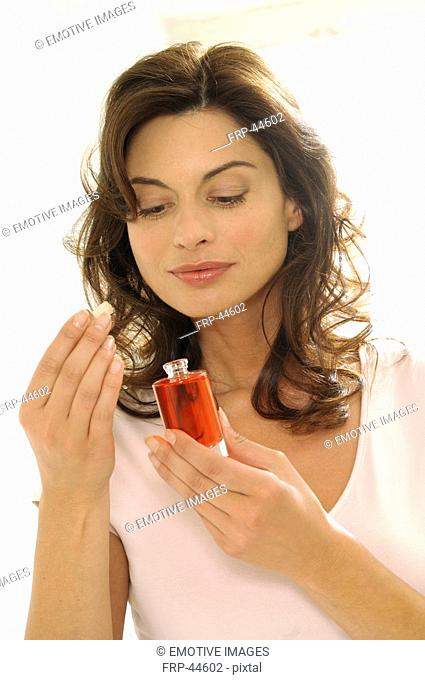 Woman is smelling on a perfum flacon