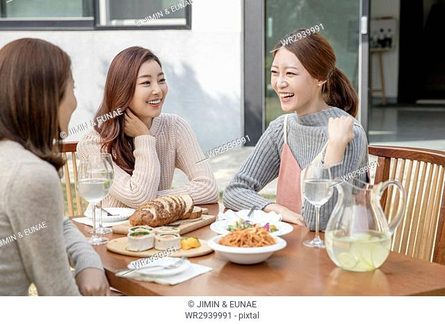 Three young smiling women at party in garden