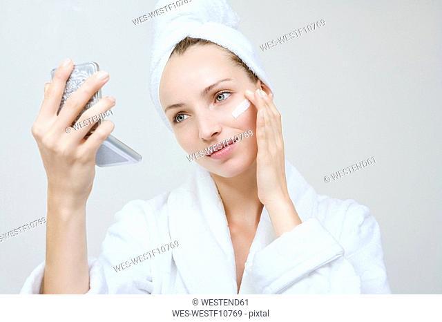 Young woman applying beauty cream, portrait