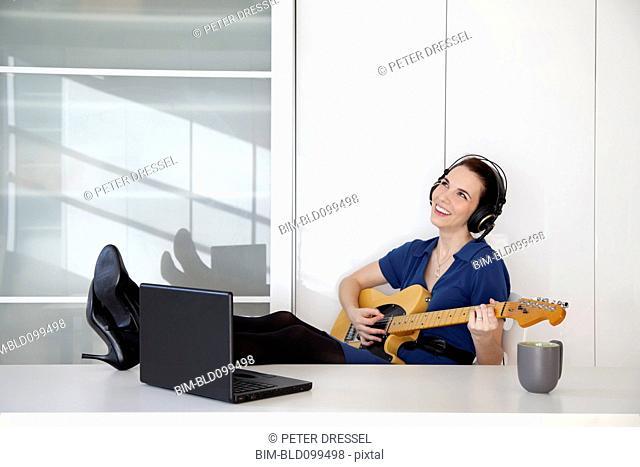Caucasian businesswoman playing guitar at desk