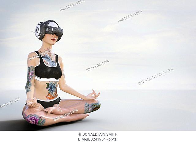 Woman with tattoos meditating and wearing virtual reality helmet