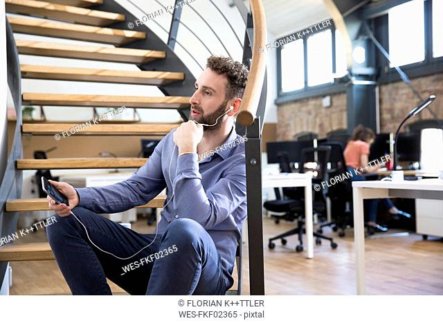 Man in modern office chatting on cell phone