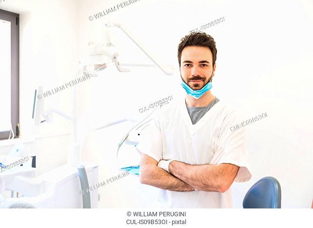 Portrait of male dentist with arms folded