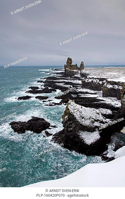 Londrangar, pair of volcanic plugs of basalt in the snow in winter, Snaefellsnes, Iceland