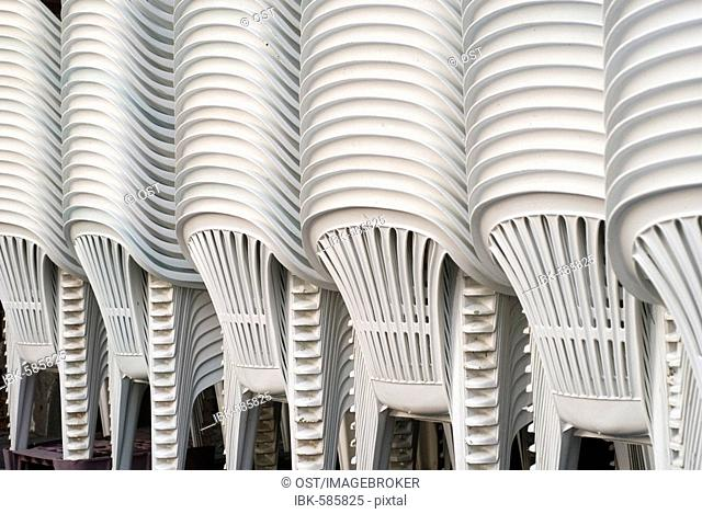 White patio chairs stacked