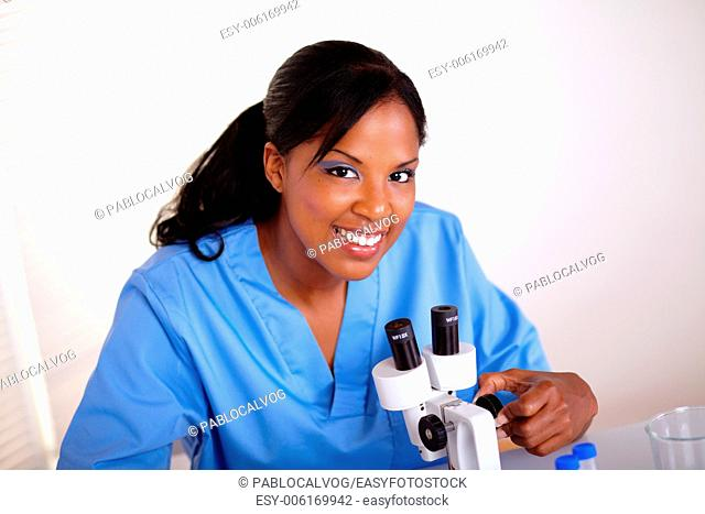 Top view of a beautiful scientific woman looking at you while working at laboratory with a microscope