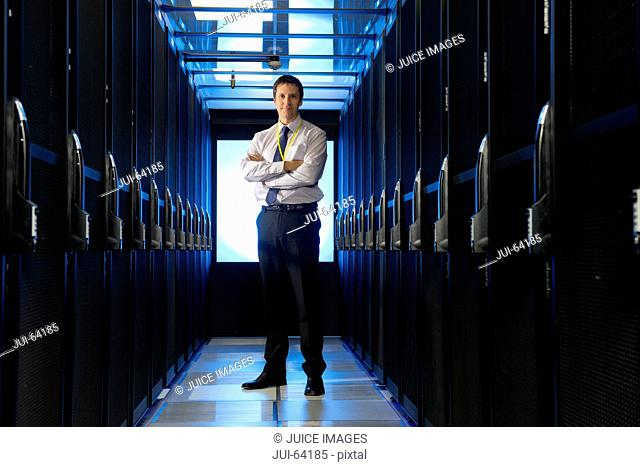 Manager standing in aisle of storage cabinets in data center