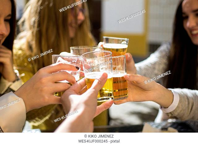 Friends toasting with beer glasses in a street cafe, close-up