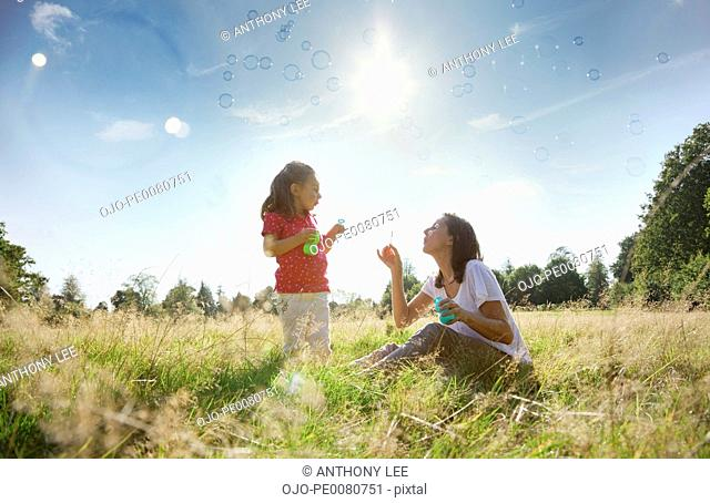 Mother and daughter blowing bubbles in sunny rural field