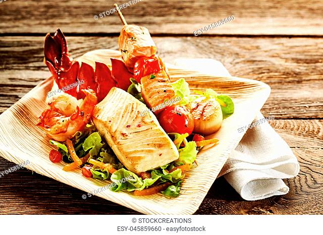 Roasted seafood salad on plate with lobster, shrimp and fish over folded napkin on wooden table