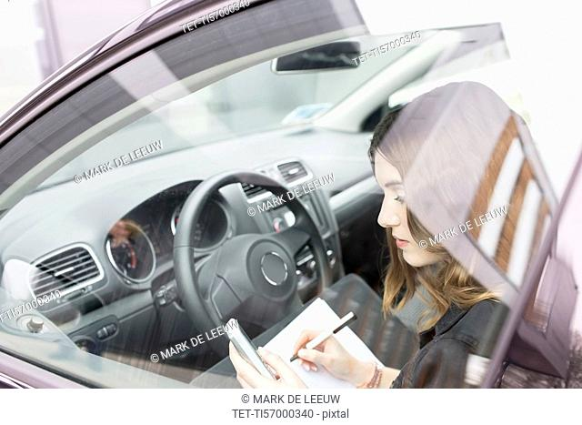 Young woman writing in notebook in car