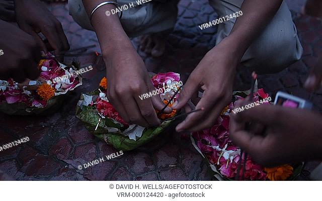 Worshiper lighting incense sticks from oil lamp at Haridwar, Uttarakhand, India