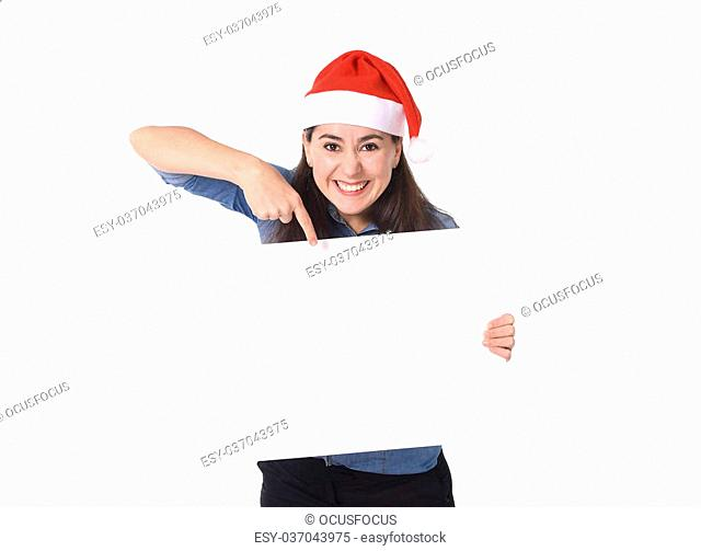 young attractive Hispanic woman wearing Santa Claus Christmas hat and blue shirt holding and p?inting blank billboard or placard sign as copy space for adding...