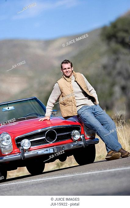 Man sitting on hood of red convertible