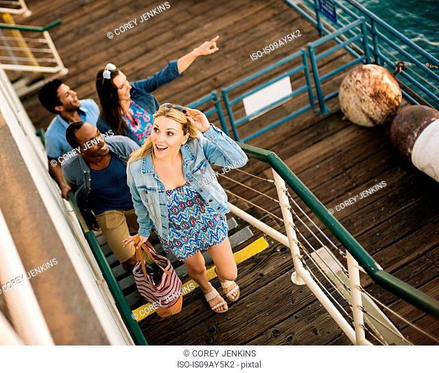 Four adult friends moving up pier stairs, Santa Monica, California, USA