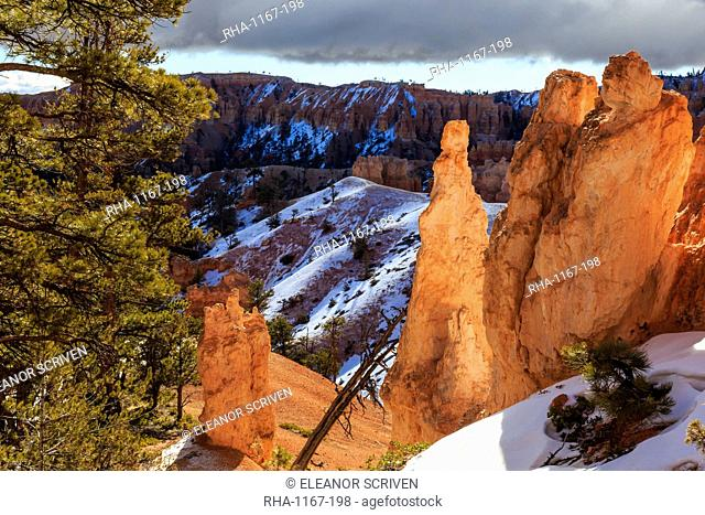 Hoodoos strongly lit by early morning sun with heavy cloud, Peekaboo Loop Trail in winter, Bryce Canyon National Park, Utah, United States of America