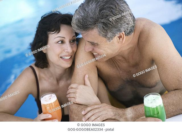 Couple having tropical drinks in pool