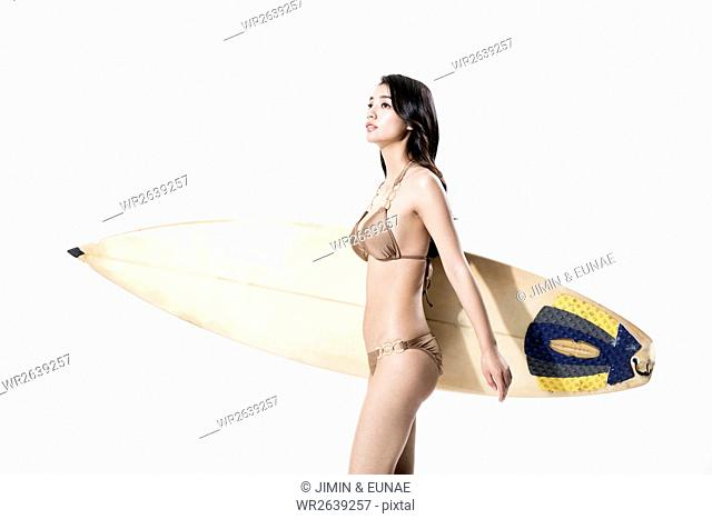 Side view of young slim woman in bikini holding surfing board