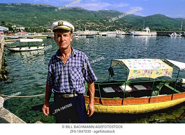 Local captain with boat in holiday town of Ohrid Macedonia