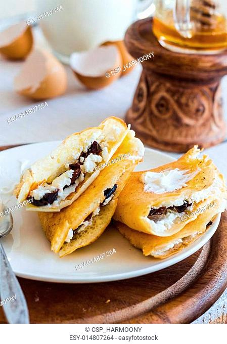 thin pancakes stuffed with cheese, prunes and sour cream, milk