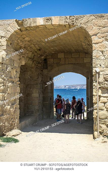 Tourists walk through the archway to one of the beaches on the island of Tabarca Spain