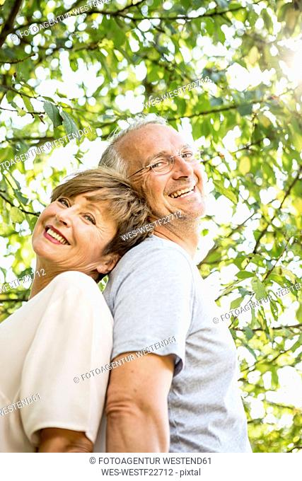 Portrait of happy senior couple back to back outdoors