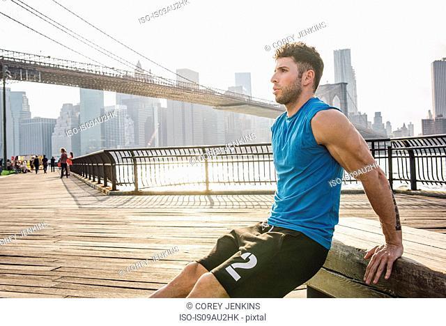 Young man doing reverse push ups on riverside, Brooklyn, New York, USA