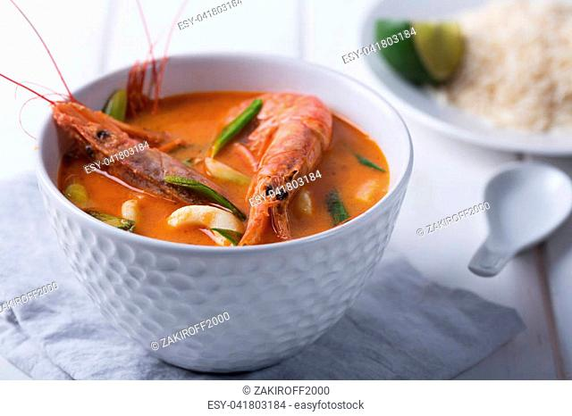 Traditional Thai soup Tom Yam prepared with shrimps, calamari and herbs