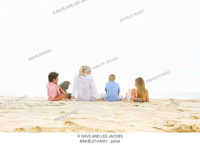 Caucasian family sitting on beach