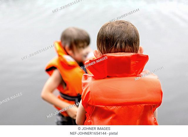 Two boys wearing live vests wading in water