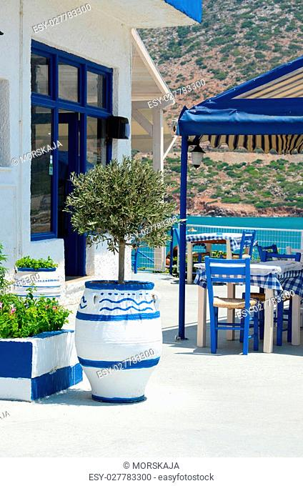 Greek tavern in traditional colors situated near the sea coast