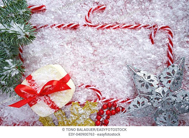 Christmas gift and candy cane frame on snow background border