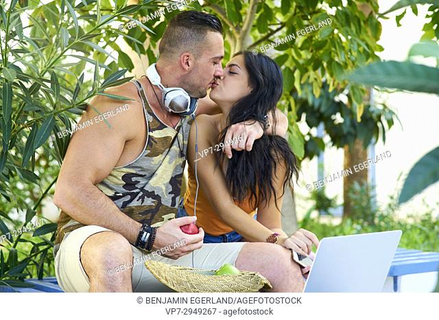young couple kissing in nature. Greek ethnicity. With headphones, laptop and healthy apples. In late summer / September. In Hersonissos, Crete, Greece