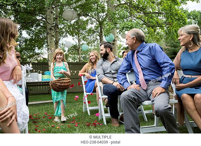 Wedding guests watching flower girl spread petals backyard