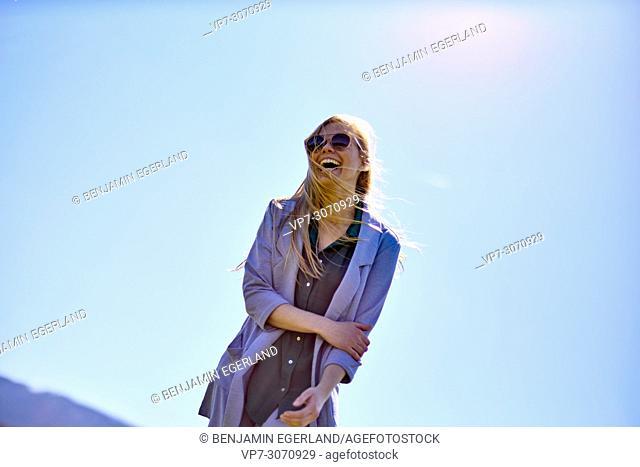 Happy woman enjoying sunny weather, against blue sky, wearing sunglasses. Waakirchen, Bavaria, Germany