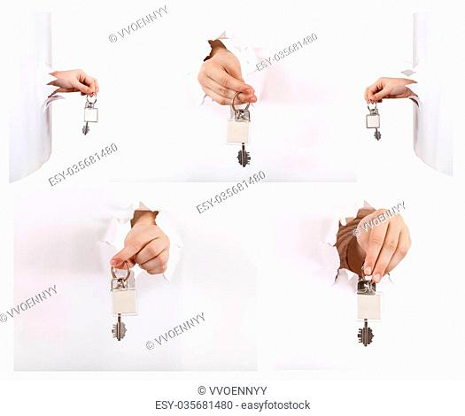 set of hands holding the keychain through a hole in a sheet of paper