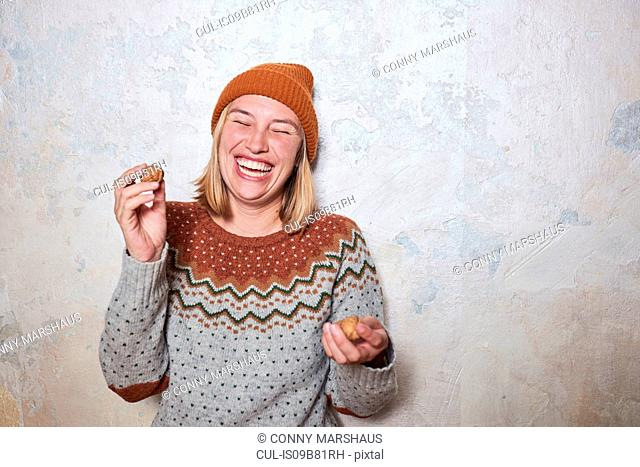 Portrait of woman wearing jumper and knitted hat, holding walnuts, laughing