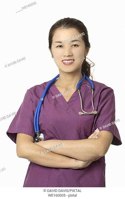 Beautiful Asian American doctor or nurse wearing blue scrubs and posing with stethoscope isolated on white background