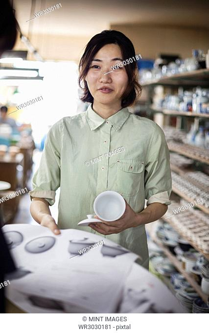 Smiling woman standing in a Japanese porcelain shop, holding drawing and cup with lid