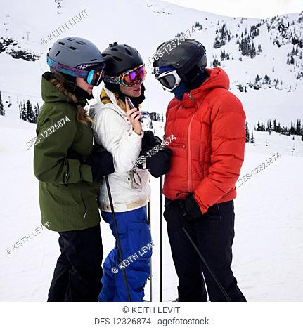 Three young adult women looking at a cell phone while standing and ready to ski at a ski resort; Whistler, British Columbia, Canada