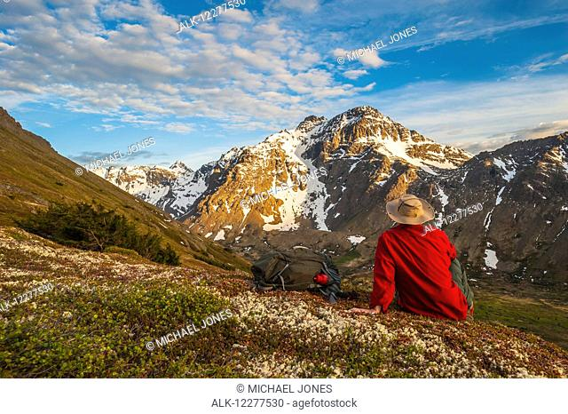 Hiker rests on a hillside overlooking Powerline Pass valley and trail, Chugach State Park, Southcentral Alaska