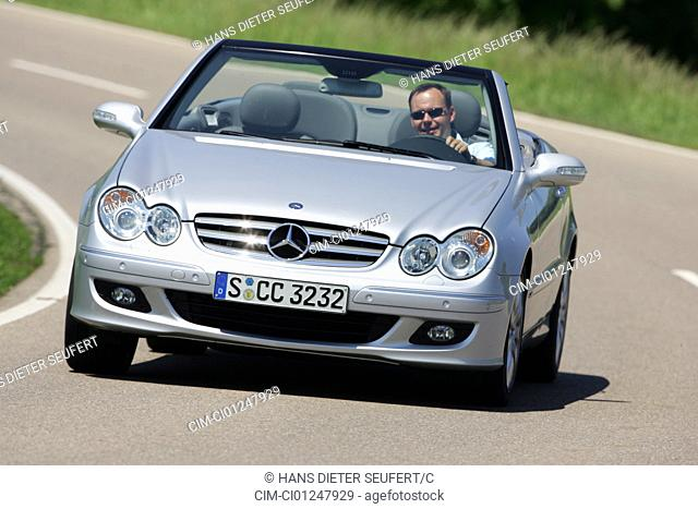 Mercedes CLK 320 CDI Convertible, model year 2005-, silver, driving, diagonal from the front, frontal view, open top, country road