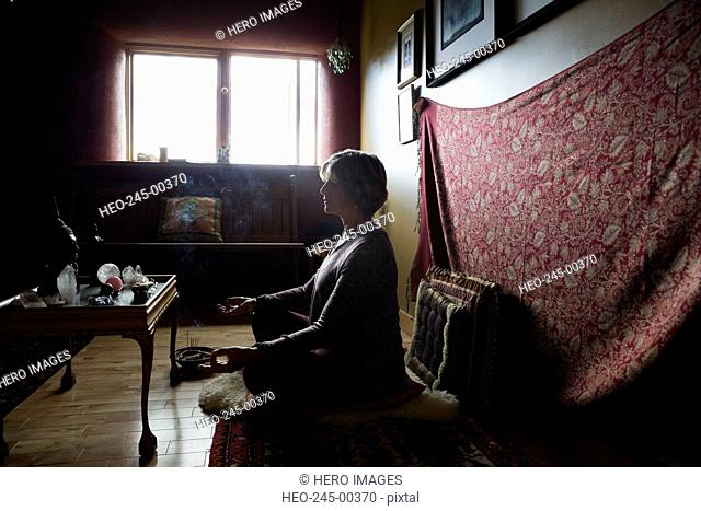 Senior woman meditating with incense