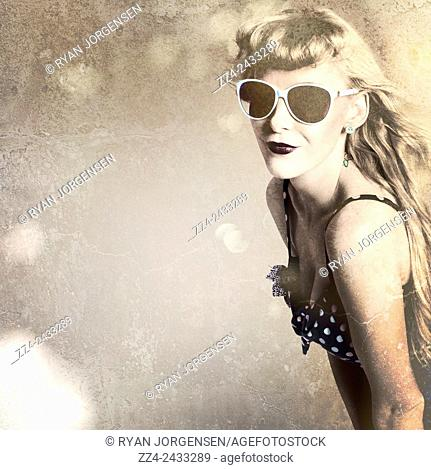 Vintage aged portrait of a stylish pin-up beauty wearing dark purple lipstick, earrings and retro shades on paper texture copyspace