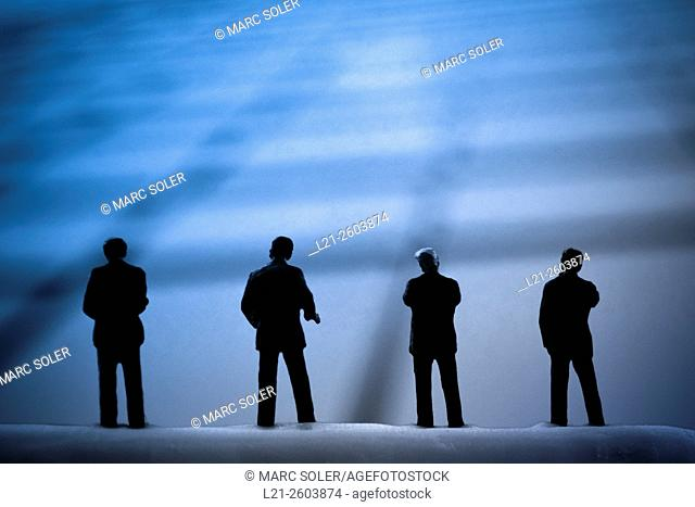 Silhouettes of men watching a blurred background of lines